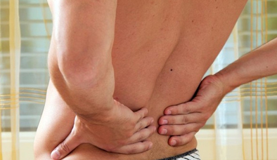 Man holding hands on lower back