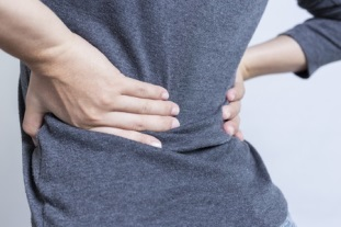 sciatica pain - woman holding lower back
