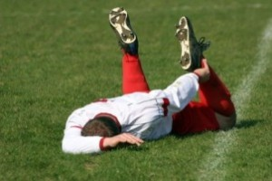 soccer playing laying on ground with sports injury