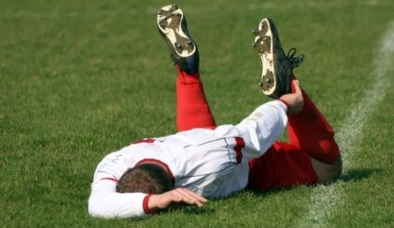 soccer-playing-laying-on-ground-with-sports-injury