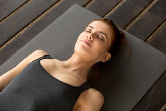 Young attractive woman lying in Dead Body exercise